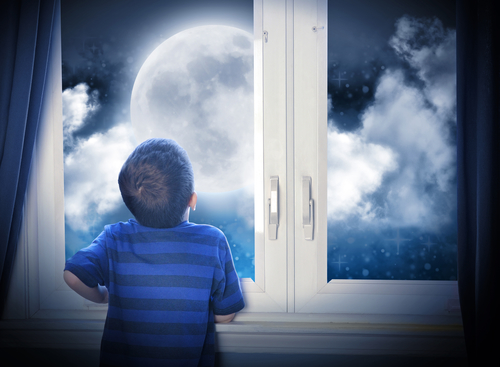 A young boy is looking out of the window at a big moon in the dark night with stars and space for an astronomy or imagaination concept.
