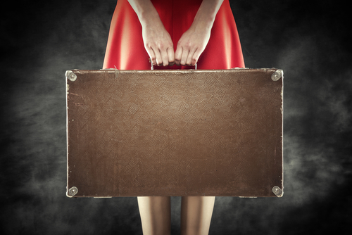 Old suitcase in hands on a dark background. Travel vintage concept.
