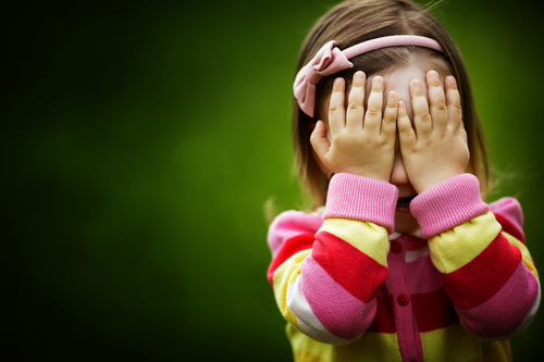 little girl is playing hide-and-seek hiding face